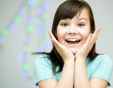 astounded: Cute girl is holding her face in astonishment
