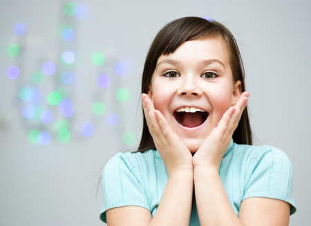 astonishment: Cute girl is holding her face in astonishment