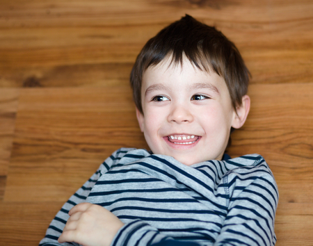 and guessing: Portrait of happy joyful laughing beautiful little boy on woden background