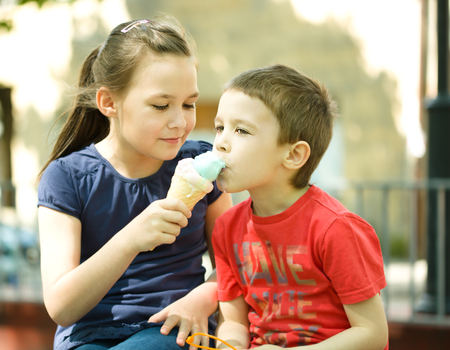 gente comiendo: La muchacha está alimentando a su hermano pequeño con helado. Al aire libre
