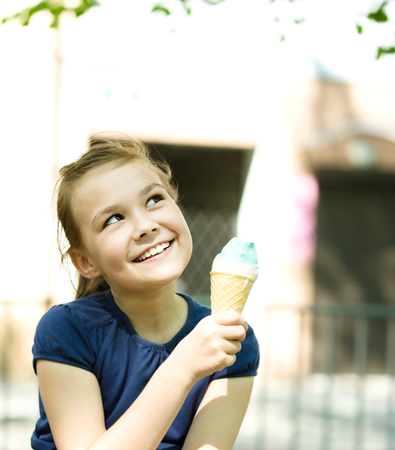 children eating: Cute happy girl is eating ice-cream