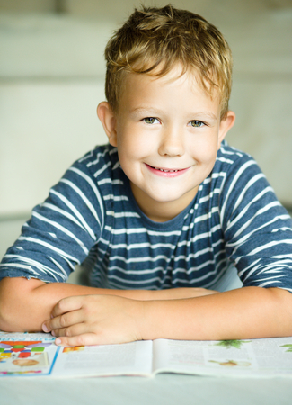 copybook: Boy is writing on his copybook in preschool Stock Photo