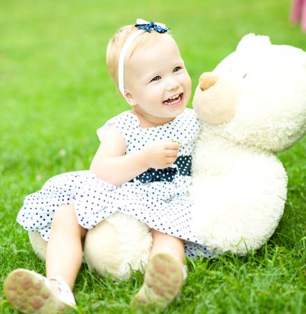 pyjama: Little cute girl is playing her teddy bear, outdoors