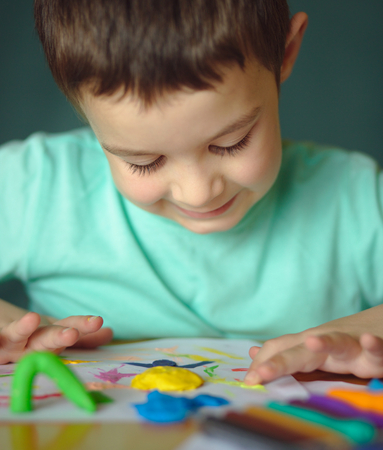 Happy boy playing with color play dough