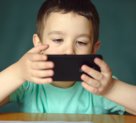 Cute boy is using smartphone. checking on her text message