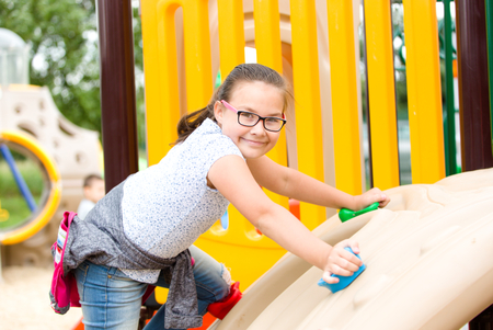 Cute happy girl is playing on playground, outdoor