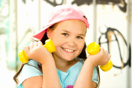 Sport healthy lifestyle concept. Sporty childhood. Teenager exercising with dumbbells
