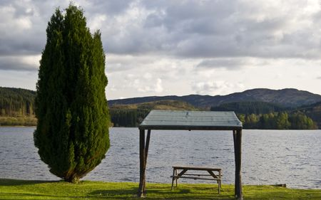 picnic table with a beautiful view over a lake photo