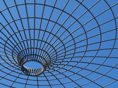 imprisoned: beautiful blue sky behind a metal framework