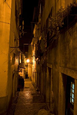 old steps leading through the old quarter Alfama in Lisbon at night photo