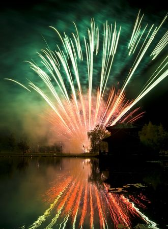 beautiful display of fireworks reflected in water photo