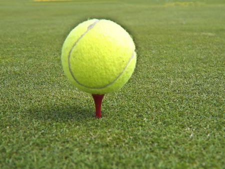 tennis ball resting on a golf tee ready for the next stroke