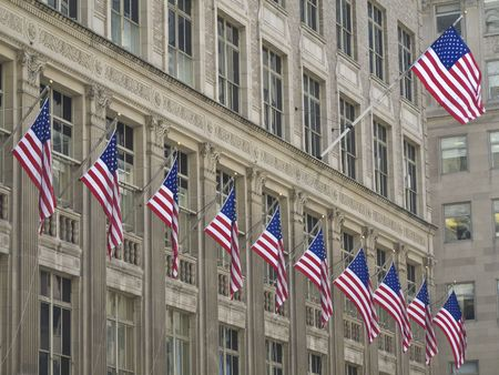 many american flags hissed on one building