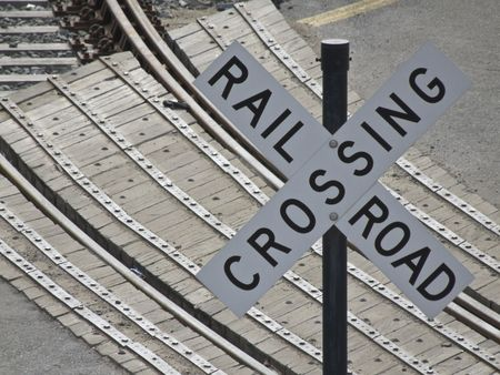 sign indicating a railroad crossing with the tracks in the background photo