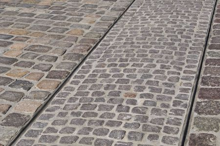 tracks of a tram on a cobblestone pavement photo