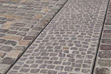 tracks of a tram on a cobblestone pavement photo