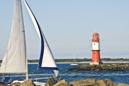 boat passing a red lighthouse on its way into the harbor  photo