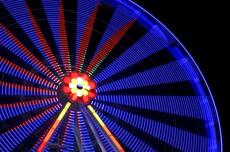 motion blur of a colorful ferris wheel at night Stock Photo