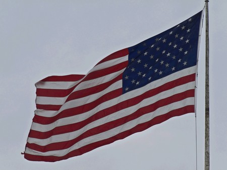 american flag in the breeze in front of a condominium photo