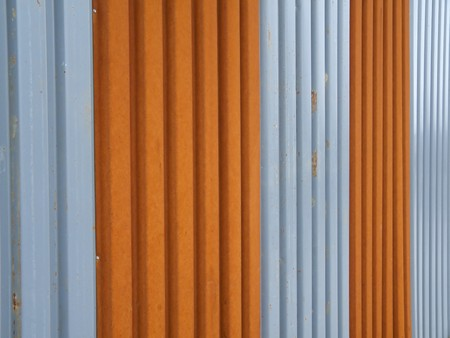 corrugated metal fence painted in orange and silver photo