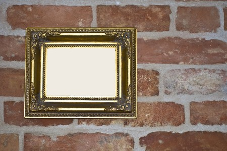 empty old golden frame on a red brick wall photo