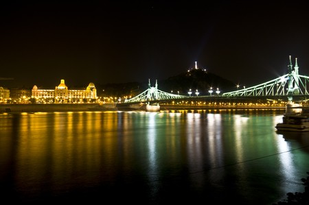 liberty bridge with the gellert hill in the background illuminated at night photo