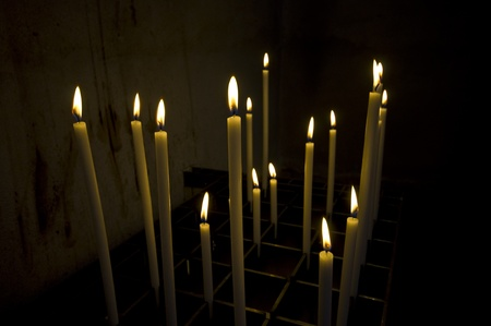 a bunch of long candles in an old dark church  Stock Photo - 10447047