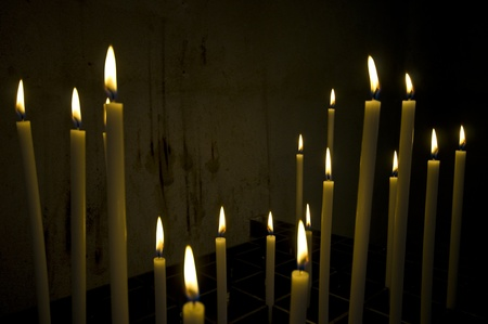 a bunch of long candles in an old dark church  Stock Photo - 10447051