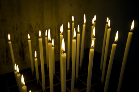 a bunch of long candles in an old dark church Stock Photo - 10447048