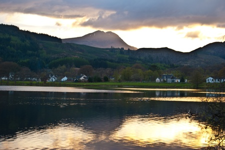 sunset behind a hill with reflections in Loch Ard photo