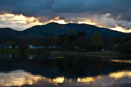 ard: sunset behind a hill with reflections in Loch Ard Stock Photo