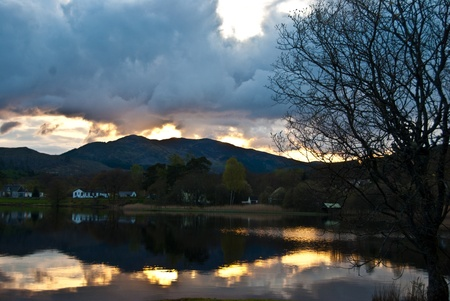 sunset behind a hill with reflections in Loch Ard Stock Photo - 13556198