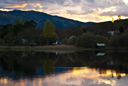 sunset behind a hill with reflections in Loch Ard Stock Photo - 13556177