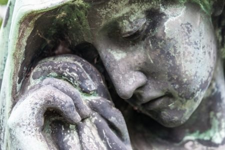 detail of a mourning sculpture on a cemetery