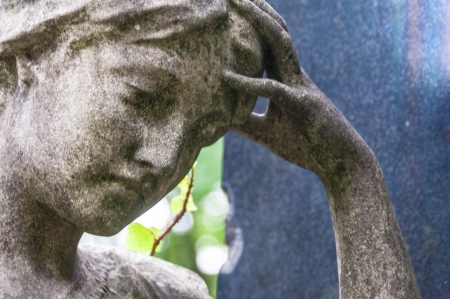 detail of a mourning sculpture on a cemetery photo