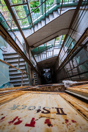 looking down an elevator shaft surrounded by stairs photo