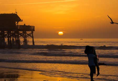 enamorados besandose: Silueta de amantes besándose en la playa y el amanecer.