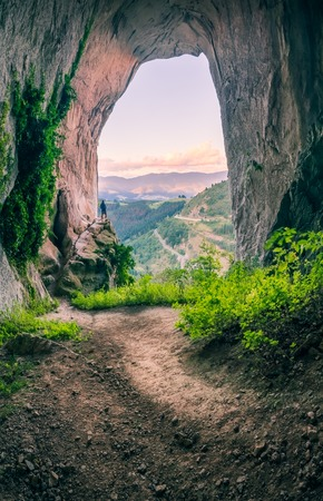 Amazing landscape in cave with beautiful colors in the clouds and person Фото со стока