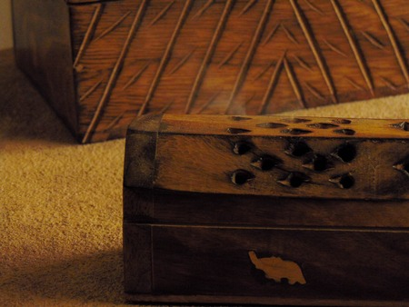 Incense box on a rustic table with a trunk of wood.