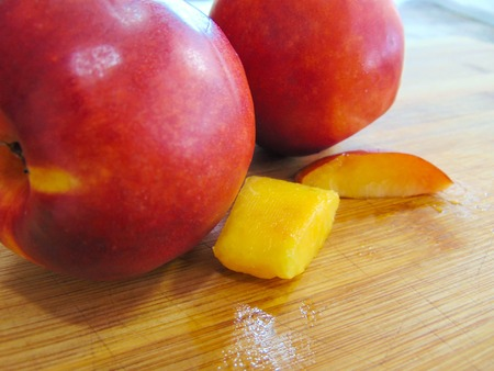 Fresh nectarines on a wooden board.