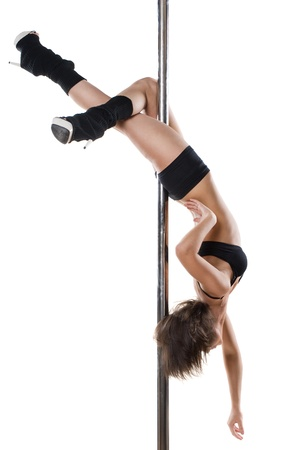 Young sexy woman exercise pole dance against a white background