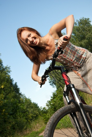 Portrait of pretty young woman with bicycle in a park smiling - Outdoor photo