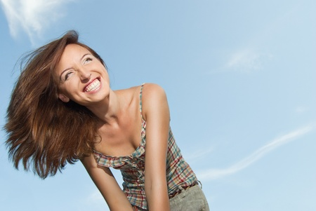 Portrait of a beautiful young woman smiling against the sky - Outdoor photo