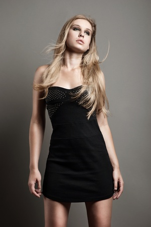 Portrait of young posing fashionable woman with smart fair hair in black dress. Studio shot.