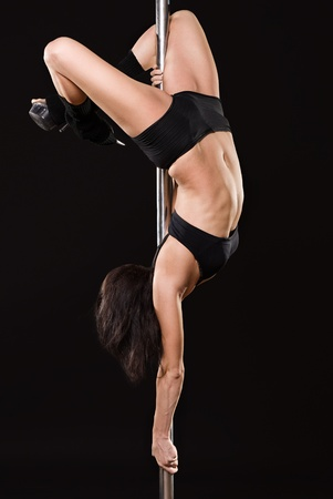 sexy woman exercise pole dance against a black background Stock Photo - 10081186