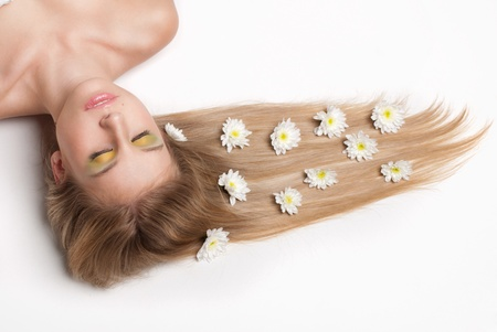 hair spa: attractive young woman lying covered with flowers