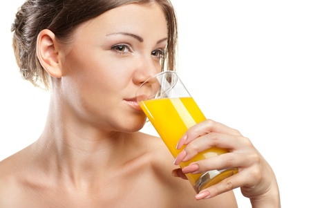 Young beautiful woman drinking orange juice isolated on a white background photo