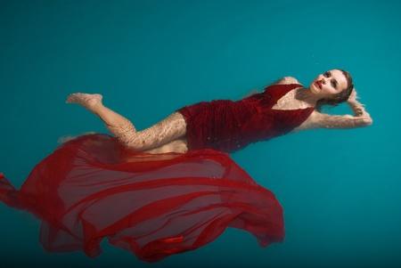若いセクシーな女性が赤いドレスを着てのプールに浮かぶ。美しさのショット