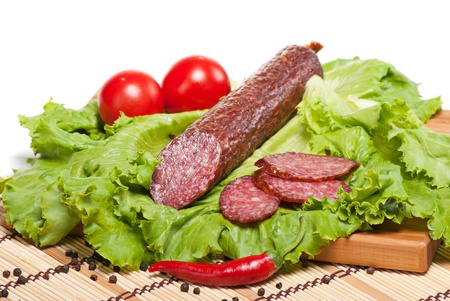 Salami with lettuce, garlic and tomatoes on white background photo