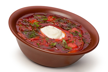 Closeup of plate of ukrainian and russian national red soup with herbs on white